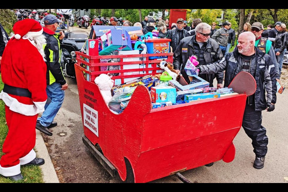 Motorcyclists who took part in the annual Toy Run bring their toy donations to the sleigh at the end of the Run in River Park.