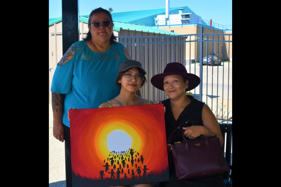 Kylie Severight, seated left, poses with her painting together with her mom Heather, seated right, and grandmother Marlene Lumberjack.