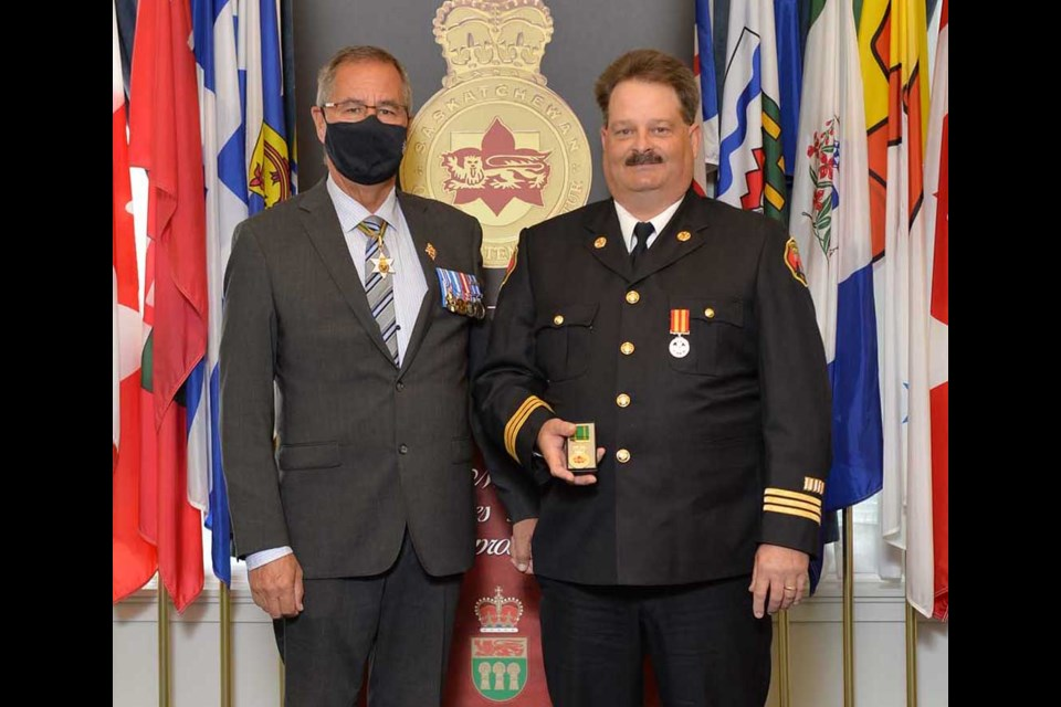 Platoon Chief Michael Kaip from the Weyburn Fire Department (at right) received a Saskatchewan Protective Services Medal from Lieutenant Governor Russ Mirasty.