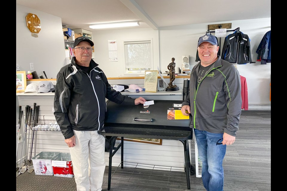 Shayne Mcauley, winner of the charcoal barbecue donated by Chimo Lumber. Veteran employee Roy Lequyer drew the lucky ticket.