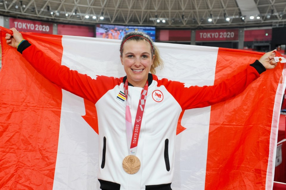 Keely Shaw proudly carries the Canadian flag and wears her Olympic bronze medal at the Paralympic Games in Tokyo.