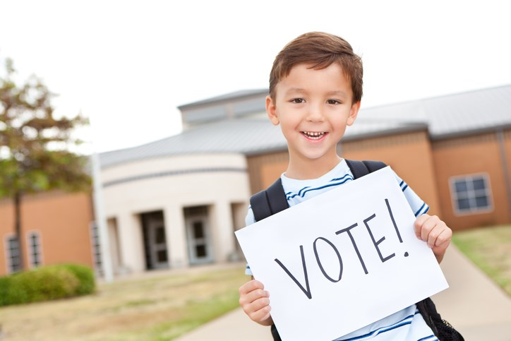 Elementary student holding vote sign