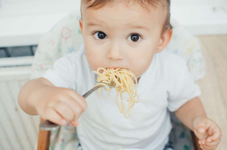 baby eating noodles stock