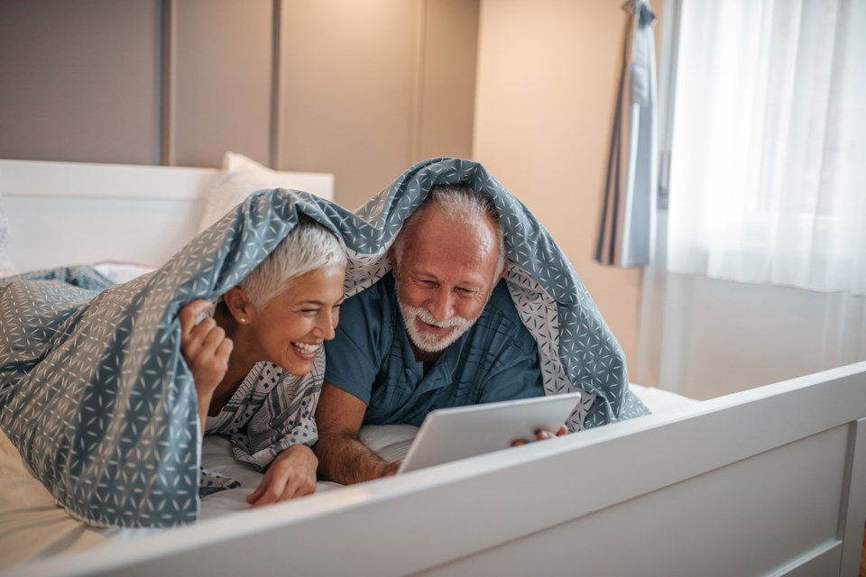 seniors snuggling with tablet stock