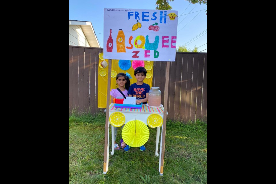 """Abrish Eman and Hanzalah Jadoon at their lemonade stand with a homemade sign reading """"Fresh Squeezed"""". Photo supplied"""