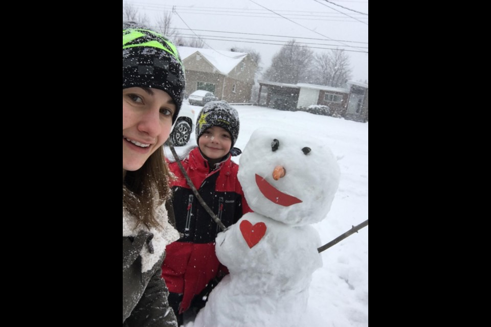 Sarah Lewis with her stepson Wyatt and one of their many custom-made snowmen.