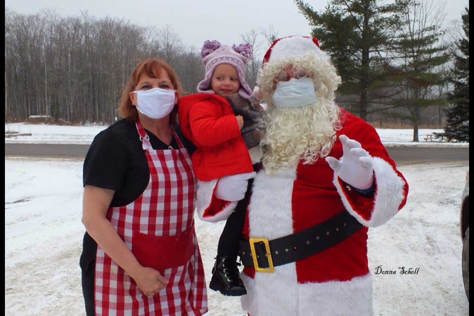 Claire Wallace (2), received a special hug from Santa and Mrs Clause (Roy and Mary Lou Eckmeier) before Santa and his entourage set out to collect for the St. Joseph Island and Area Food Bank