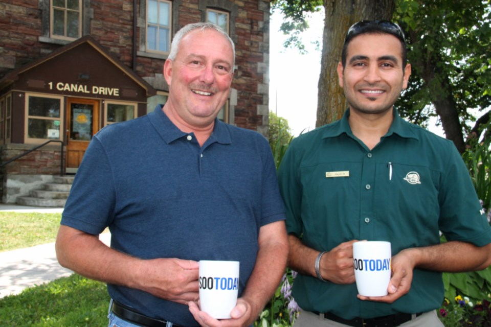 Barry Guzzo and Bachir Nedjar, Parks Canada project managers at the Sault Ste. Marie Canal National Historic Site, with their complimentary SooToday mugs, Aug. 1, 2018. Darren Taylor/SooToday