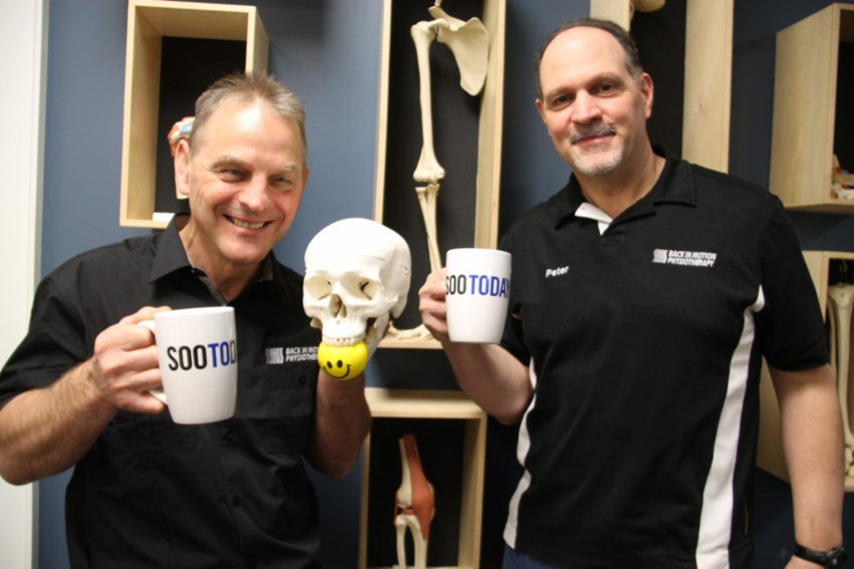 Andre Riopel, registered physiotherapist and Back in Motion founder, and Peter DeAngelis, Back in Motion registered physiotherapist (and friend!), with their complimentary SooToday coffee mugs, Dec. 14, 2018. Darren Taylor/SooToday