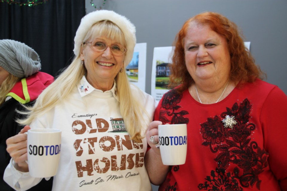 Mayla Brauner and Myril Lynn Brason-Lediett, Ermatinger-Clergue National Historic Site volunteers, pictured with their complimentary SooToday coffee mugs Dec. 21, 2018, partnered with ARCH volunteers and staffed Station Mall's gift wrapping centre this season, proceeds going to both organizations. Darren Taylor/SooToday
