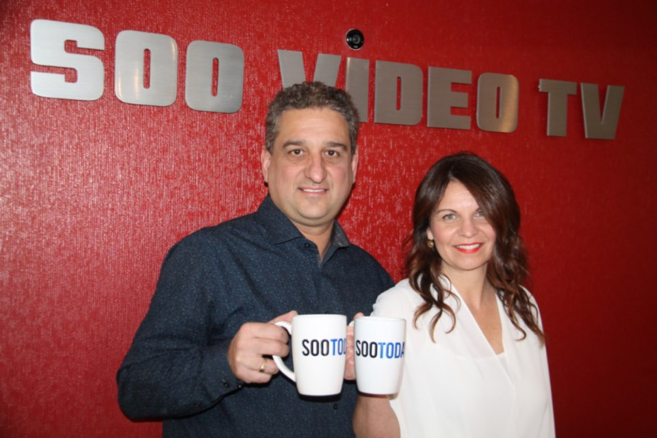 George DiBerardino, Soo Video TV owner/operator, and wife Julie DiBerardino, Soo Video TV administrative assistant, with their complimentary SooToday mugs, Jan. 18, 2019. Darren Taylor/SooToday