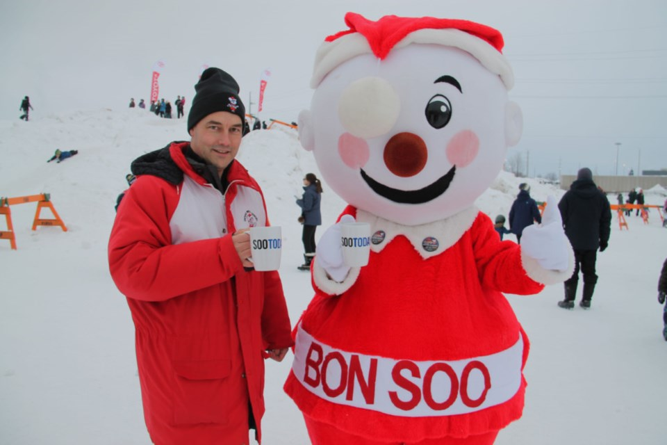 Rob Woolley, Bon Soo support team member, and Mr. Bon Soo take a coffee break during Bon Soo activities with their complimentary SooToday mugs, Feb. 2, 2019. Darren Taylor/SooToday