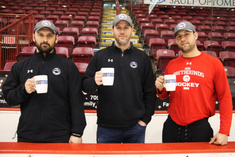 Jamie Tardif, Soo Greyhounds assistant coach, John Dean, Soo Greyhounds head coach and Jordan Smith, Soo Greyhounds associate coach behind the bench with their complimentary SooToday mugs, Feb. 6, 2019. Darren Taylor/SooToday