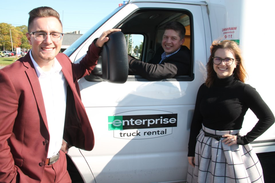 Jordan Connors, the Sault's Enterprise Truck Rental manager, with Lauren Moore, assistant manager, joined by Matt Ross (Ottawa-based Enterprise group truck manager, seated at the wheel of an Enterprise van), Oct. 9, 2019. Darren Taylor/SooToday
