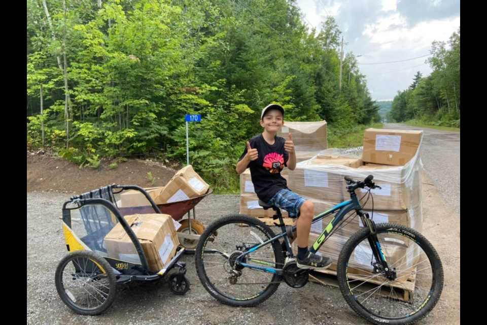 Wyatt Mageran with boxes of 'message bottles' ready for purchase and to be sent to people worldwide who need a lift during the pandemic, purchased by his stepmother Sarah Lewis for 4the Love