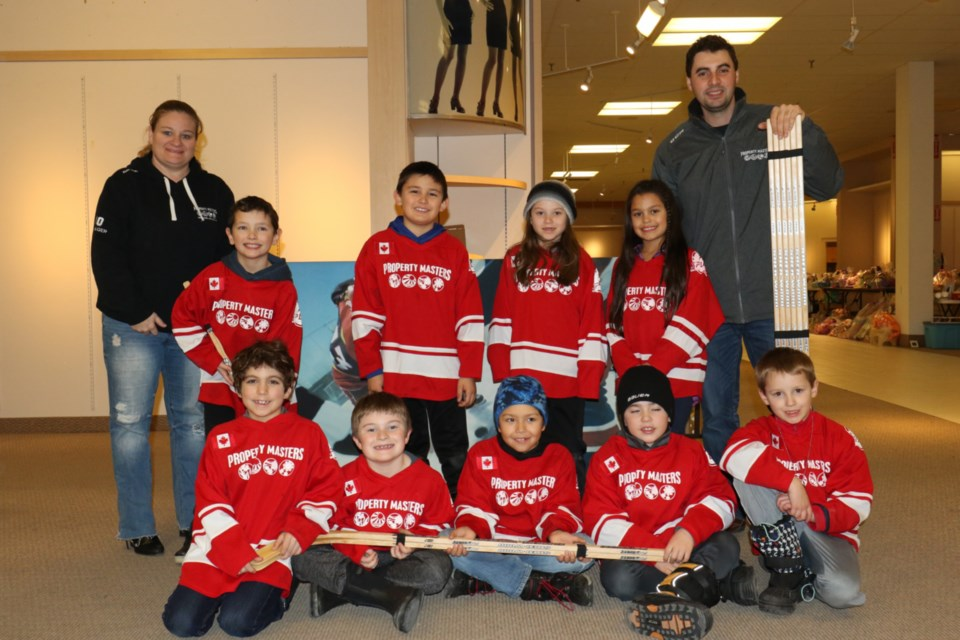 Members of the Property Masters Novice Major A hockey team joined coach Chris Miller, right, and manager Amy Tolin, left, to present Christmas Cheer with a donation of new hockey sticks. Children on the team also rounded up some used hockey gear for the annual campaign. James Hopkin/SooToday