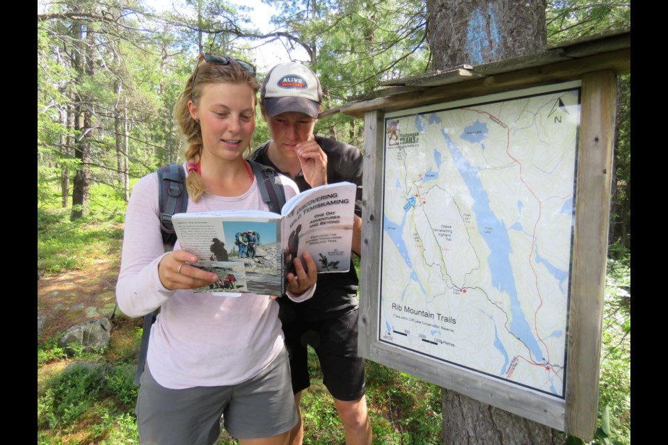 Ali and Mike look at the orientation map at the top of Cliff Lake this is a day trip paddle and hike adventure.