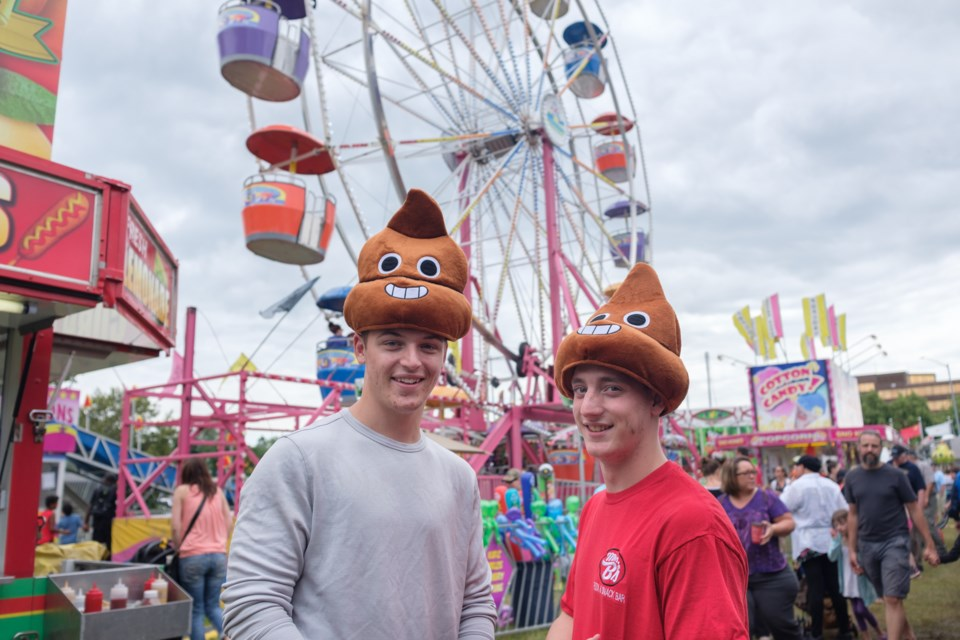 'Just a couple of...' (From left) Gage Stephney and Jesse Soltys wear poo emojis on their heads after winning them at the Rotaryfest midway on Sunday. Game operators say poo emoji plush toys and hats are the sought-after prizes this year. Jeff Klassen/SooToday