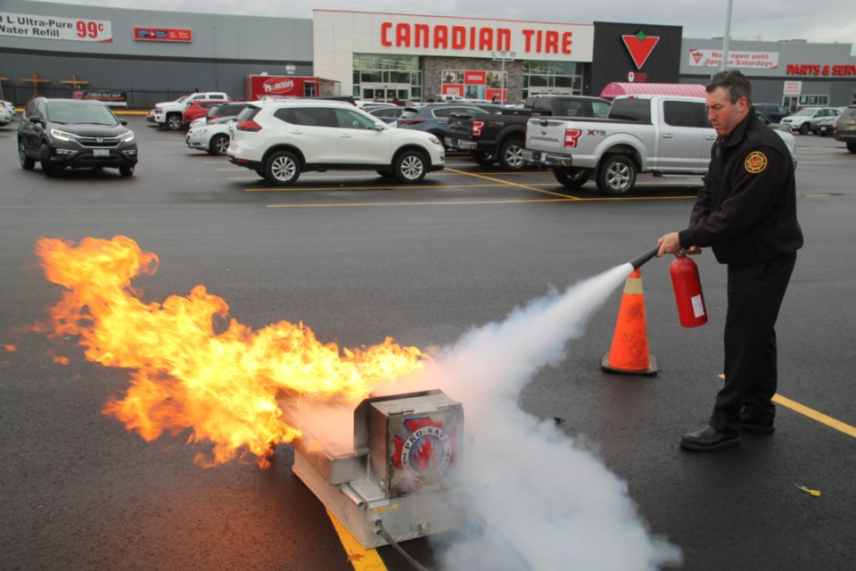 Aaron Gravelle, Sault Fire Services public education officer, demonstrates how to use a fire extinguisher, Oct. 12, 2019. Darren Taylor/SooToday