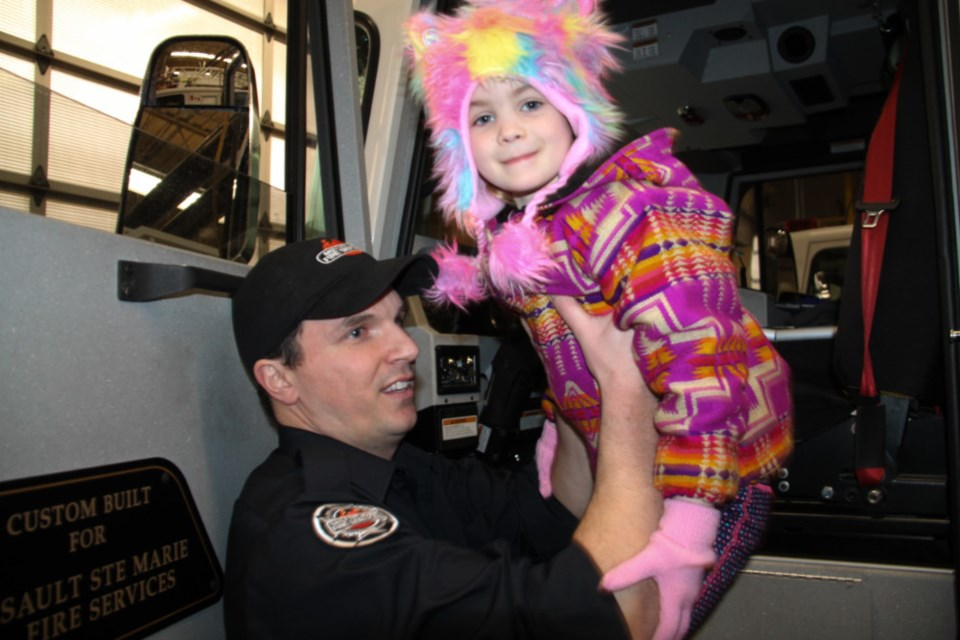 Neil Brockelbank, Sault firefighter, gives a lift to Faelynn O'Brien, Dec. 30, 2018. Fire Station tours were held for children and their parents at Number 1 Fire Hall at 72 Tancred St. as part of 28th Community Christmas for Children activities, which continue to Jan. 5, 2019. Darren Taylor/SooToday