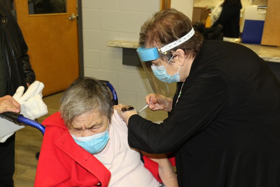 Virginia McCoy, an 82-year-old member of Batchewana First Nation, receives the first dose of the Moderna vaccine at the Sault Ste. Marie Indian Friendship Centre Thursday.