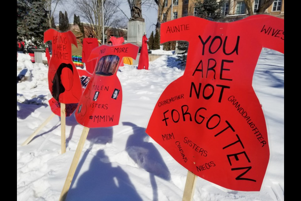 Signs in the shape of red dresses adorn Queen Street during a 2020 Missing and Murdered Indigenous Women and Girls  memorial march in Sault Ste. Marie. (James Hopkin/SooToday)