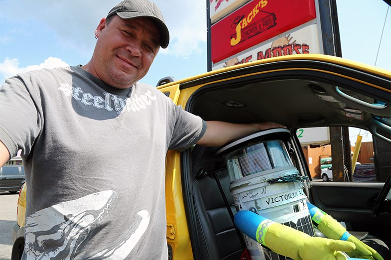 Henry Lewis seen August 5, 2014 with hitchBOT in the passenger seat of his car. SooToday.com/Kenneth Armstrong