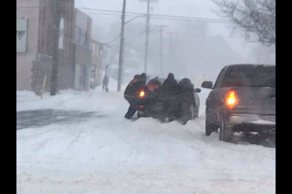 Josh and Bethany Jansen took the time to help push vehicles out of Monday record breaking snowfall. Photo supplied