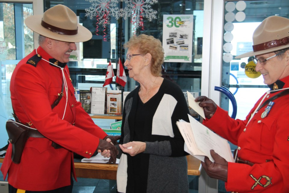 Fulfilling a long-held wish to visit the Canadian Bushplane Heritage Centre, Ann Roger, a Manitoulin Island native now living in southern Ontario, is greeted at the museum by Sault RCMP detachment Constables Earl Dalphy and Dan Chevalier, Dec. 2, 2019. Darren Taylor/SooToday
