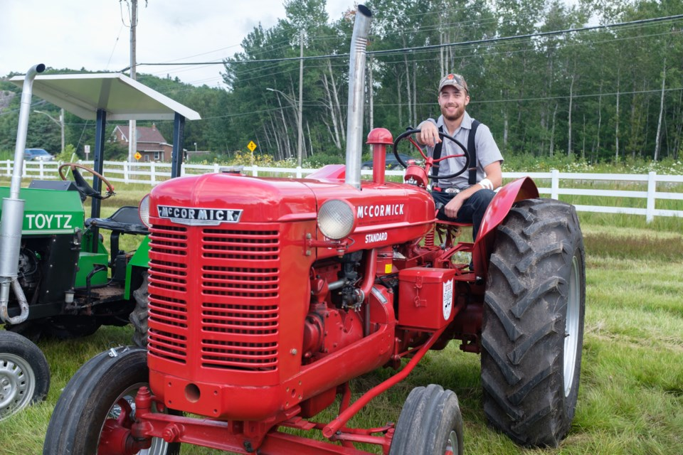 Daniel Black sits on his great grandfather Fred Woolley's 1953 McCormick W-4 tractor at the 2017 Prince Township Tractor Cruise on August 5. Jeff Klassen/Sootoday