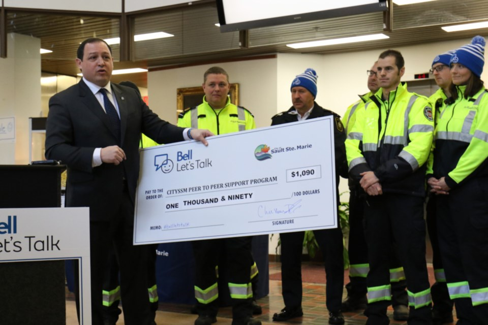 Mayor Christian Provenzano presents a $1,090 cheque to the peer-to-peer support program for first responders during the Bell Let's Talk flag raising ceremony at city hall Wednesday. The money was raised for the program by city staff. James Hopkin/SooToday