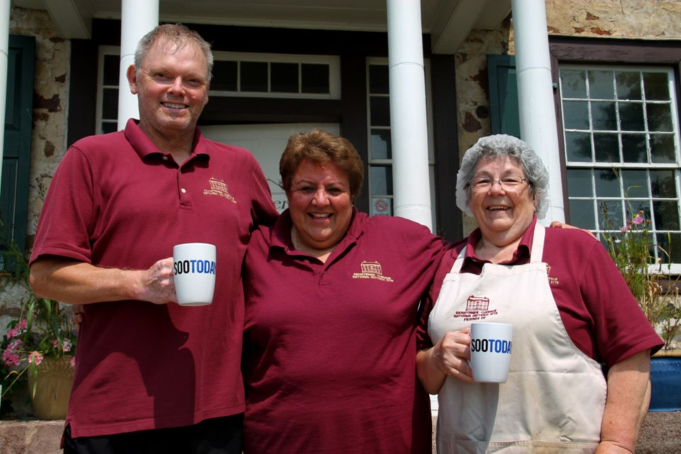 Ian Ganton, Ermatinger-Clergue National Historic Site historic interpreter, Kathy Fisher, site curator, and Alma Kasch, site cook, with their complimentary SooToday mugs, Aug. 13, 2018. Darren Taylor/SooToday