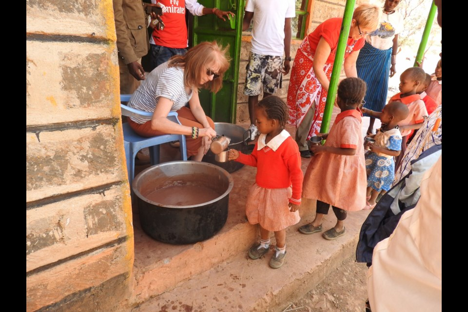 Sylvie Mackey, left, and Sheree Wilson, right, serve uji - a Kenyan porridge - in Namuncha, Kenya. Photo supplied by Holly Wickett