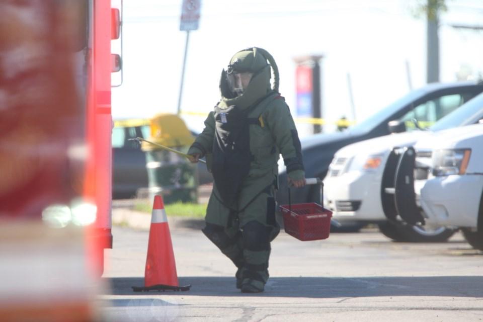 An officer returns from the city police station wearing a protective suit. Kenneth Armstrong/SooToday