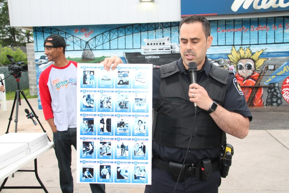 Constable Sonny Spina, Sault Ste. Marie Police Service, with vintage Police cards at a mural presentation ceremony at the Mac's Convenience Store location, 647 Second Line West, June 22, 2017.  Darren Taylor/SooToday