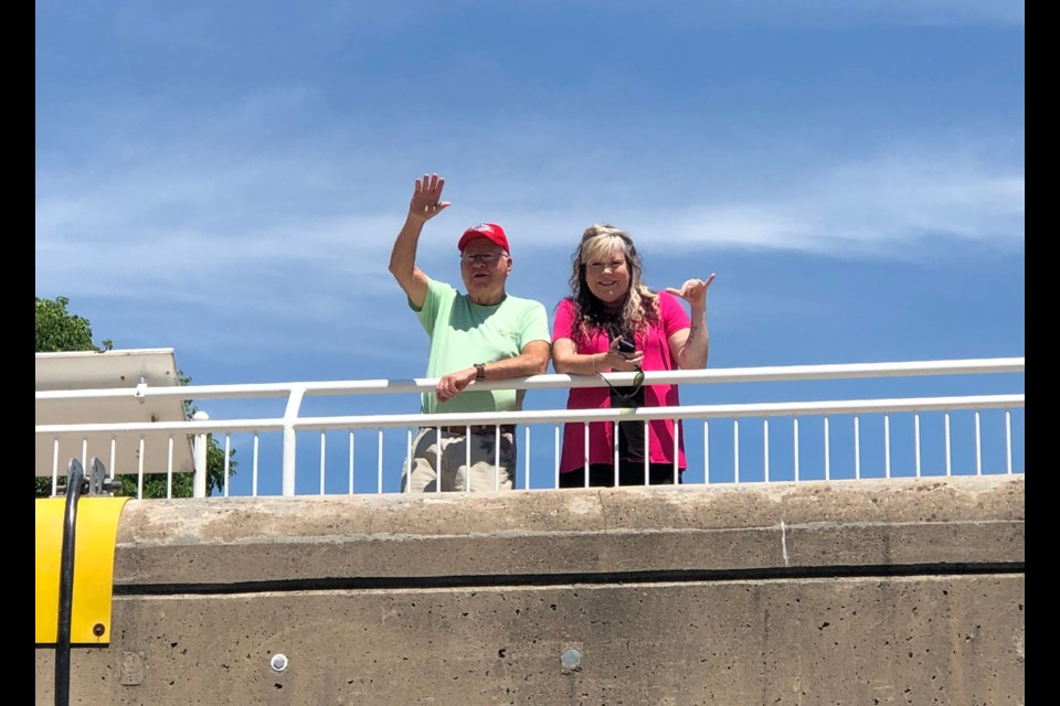 Kerry Mackan Marshall, and Stan Marshall wave to Shelley Marshall Shankle as Marshall Shankle passes through the locks on the Soo Locks boat tour Tuesday.