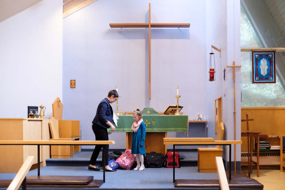 Rev. Pamela Rayment and Lily, 6, in front of the altar next to a line of backpacks waiting to be blessed at Emmaus Anglican Church on Sunday. Jeff Klassen/SooTday