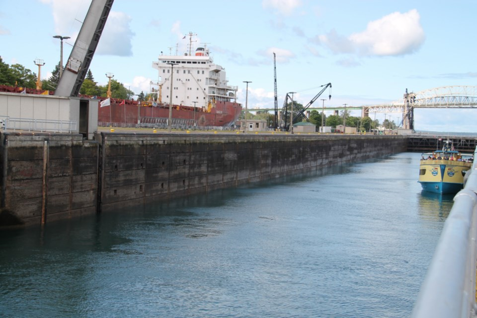 A tour boat passes through Sault Michigan's Poe Lock while Canada Steamship Line freighter Oakglen passes through the MacArthur Lock, Aug. 23, 2019. Darren Taylor/SooToday