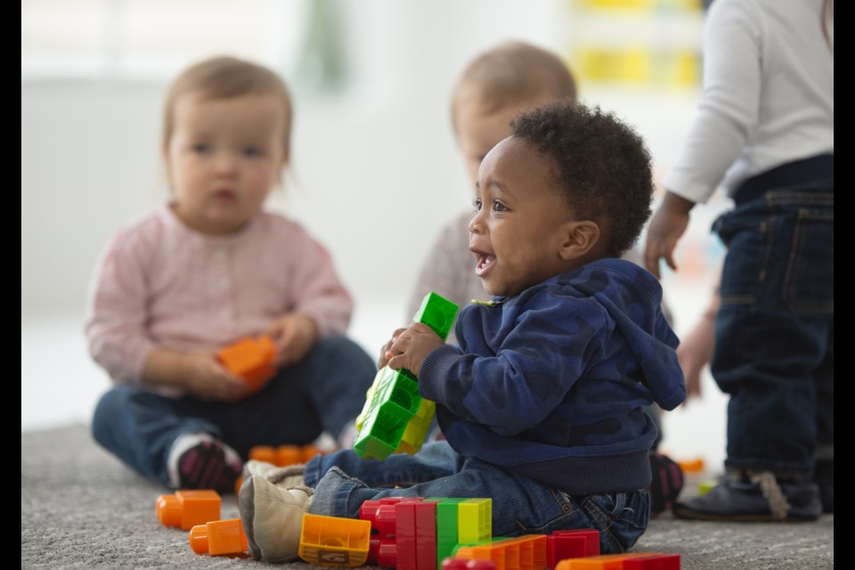 A group of toddlers sit and play with blocks. This age group is the hardest to find day care spots for, locals say.