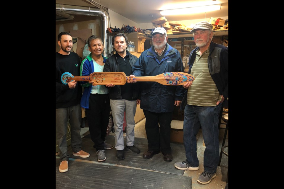 Portage crew Lenny Rubenovitch and Art Harry presenting the Men's shed members with a paddle for their support.