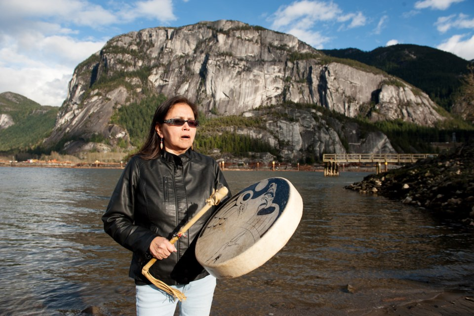 Squamish Nation knowledge keeper Tsawaysia Spukwus drums in front of the Stawamus Chief,