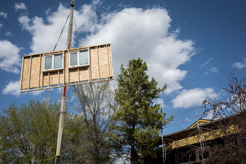 HEAVE HO – Crews hoist a premade wall panel into place during the 2019 retrofit of the Sundance Housing Co-Op. By using premade wall panels, crews were able to renovate the outside of the home without evicting the people living inside it.  PETER AMERONGEN/Photo