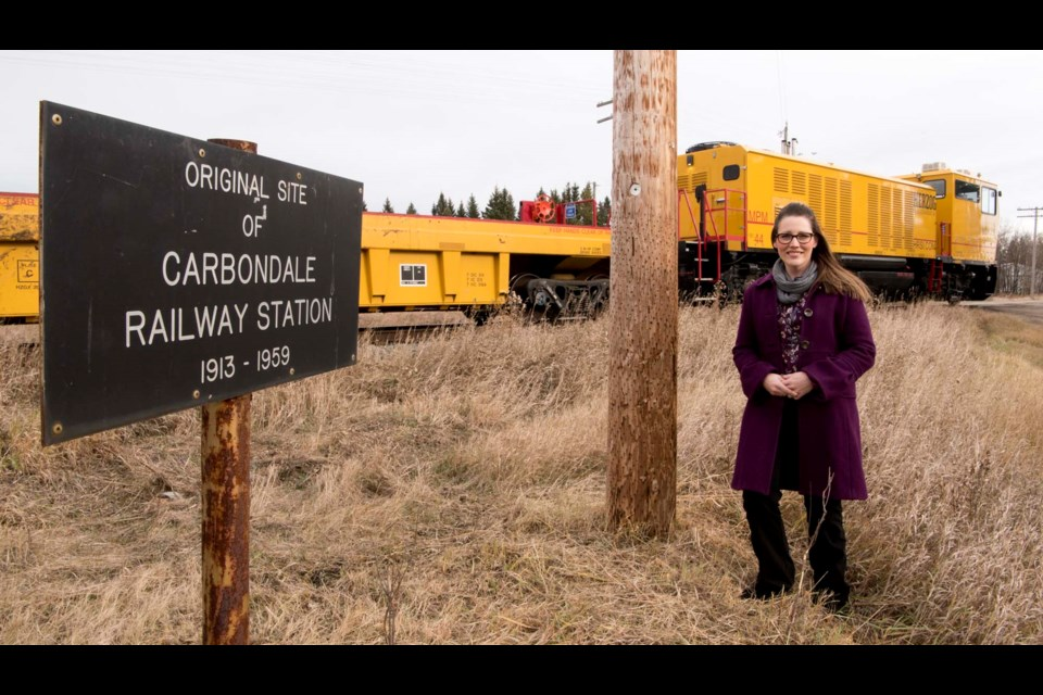 HISTORIC SITE – Carbondale resident Shannyn Rus stands near a marker that indicates how the Carbondale Rail Station once stood near her Sturgeon County home. The station was destroyed in a train crash 60 years ago this month. KEVIN MA/St. Albert Gazette