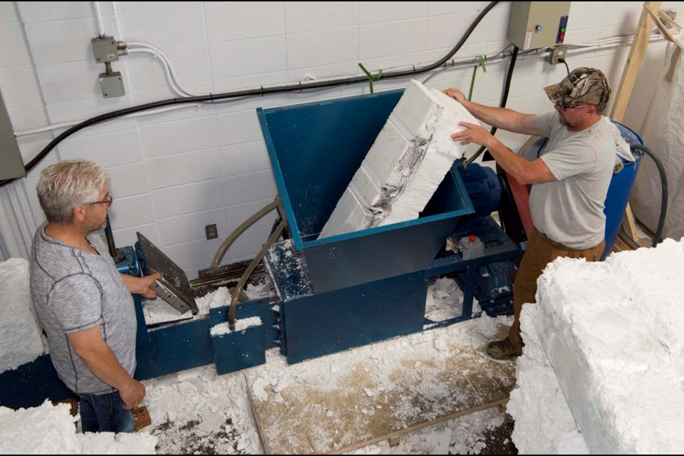 GRIND AND CRUSH — Styro Re Cycle cofounders Don Fink, left, and Leighton Larson run a chunk of Styrofoam through their compactor. The machine uses a grinder and an auger to compress Styrofoam to 1/40th of its original size to create dense bricks like the one in the lower right. KEVIN MA/St. Albert Gazette