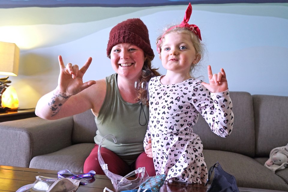 Louise Berezowsky and her five-year-old daughter Clara signing 'I love you' at their home in St. Albert. Clara lives with CHARGE syndrome, a rare genetic syndrome seen in 1 in 10,000 births. BRITTANY GERVAIS/St. Albert Gazette