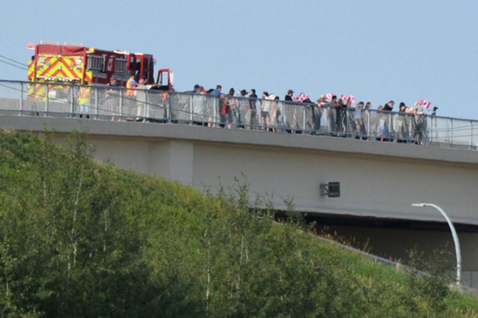 Volunteer extras waved flags on an overpass for a scene for Fallen Heroes: Their Journey Home. SCOTT HAYES/St. Albert Gazette