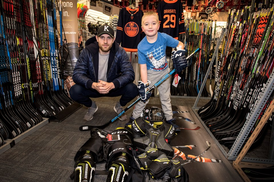 GEARED UP FOR HOCKEY – Leon Draisaitl of the Edmonton Oilers joined Mercer Fink of Red Deer at St. Albert Source for Sports to assist the eight-year-old, with the novice B Red Deer Nighthawks, choose $1,000 worth of hockey equipment on Thursday. Kentwood Ford, Team Ford and St. Albert Source for Sports partnered together to donate the equipment to the winner of a write-in contest explaining the need for the equipment.