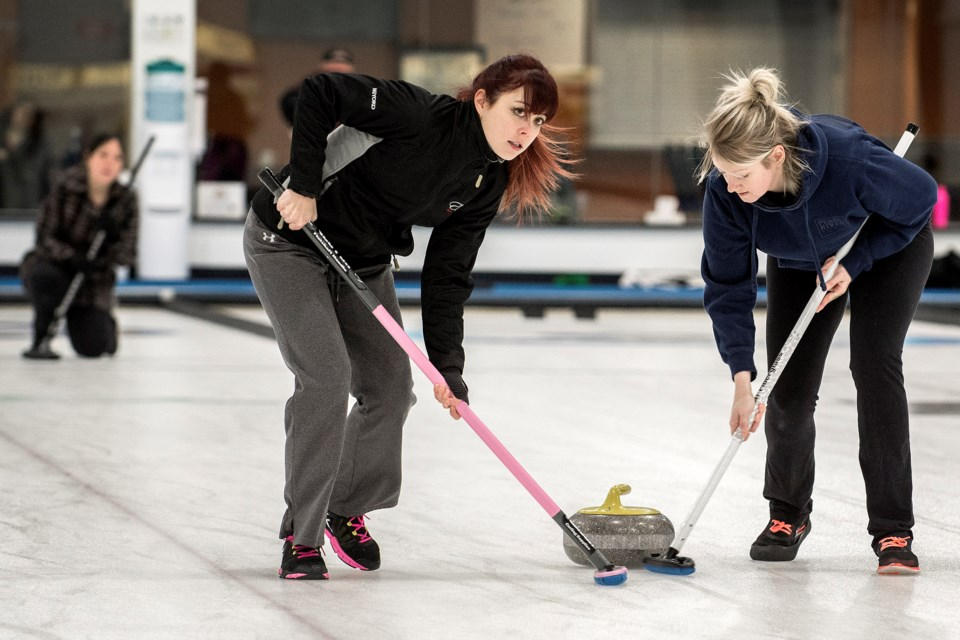 SLIDING ALONG – Miyoko Sawada, left, and Sydney McLellan sweep skip stone as Kimiko Sawada eyes the line during action in the St. Albert Fraternal Order of Eagles' weekly Sunday morning league at St. Albert Curling Club.