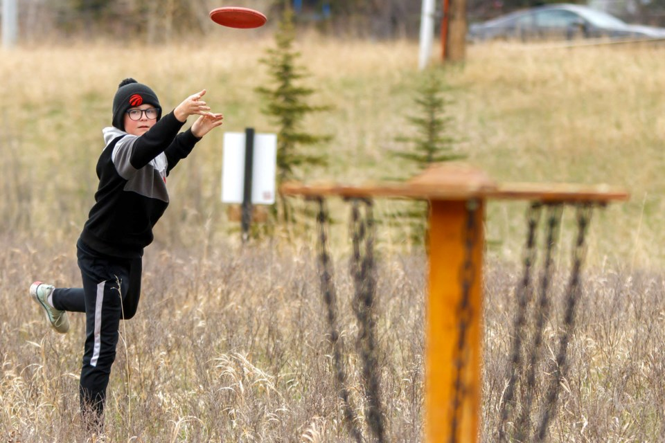 THROW LONG AND PROSPER: Beckett Ashworth, 12, putts towards the basket at the Town of Cochrane Dic Golf Course on Monday (May 11). (Chelsea Kemp/The Cochrane Eagle)