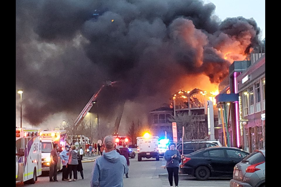Fire trucks battle back flames at the top of the building. APRIL HUDSON/Photo